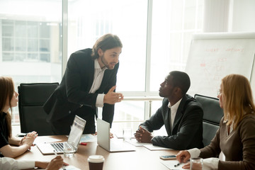 Angry mean boss scolding incompetent employee for bad work results at diverse group meeting, company executive reprimanding admonishing office worker for business mistake at multiracial team briefing