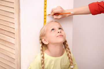 Young woman measuring her daughter's height at home