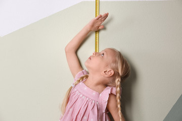 Little girl measuring her height near color wall
