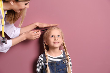 Doctor measuring little girl's height on color background