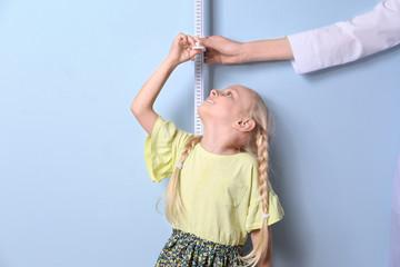 Doctor measuring little girl's height on light background