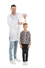 Doctor measuring little boy's height on white background