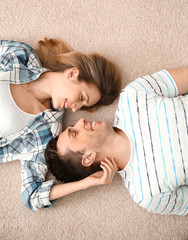 Lovely young couple lying on cozy carpet at home