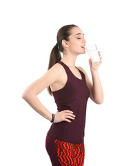 Beautiful young woman in sportswear drinking milk on white background