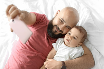 Dad taking selfie with his little son on bed