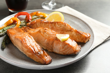 Tasty cooked salmon with vegetables on plate, closeup