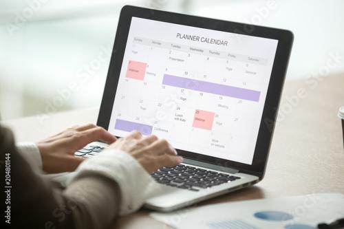 Businesswoman planning day using digital planner or calendar
