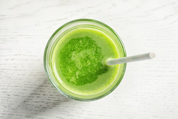 Glass with delicious detox juice on light background, top view