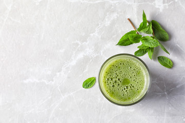Glass with delicious detox juice and mint on light background, top view