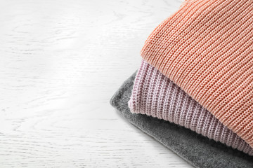 Stack of warm knitted clothes on light background