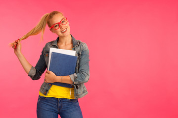 Beautiful young happy woman in yellow t shirt holds folder pose over pink background