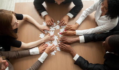 Diverse team people assembling jigsaw puzzle, multiracial group of black and white colleagues engaging in successful teamwork finding business solution, corporate unity teambuilding concept, top view