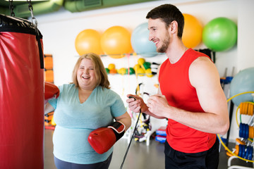Portrait of happy obese woman hitting punching bag and laughing while exercising in gym with personal fitness coach