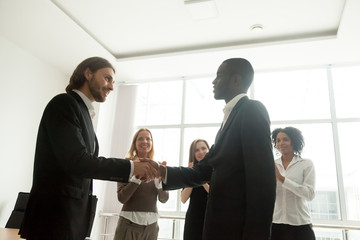 Boss and team appreciating successful black businessman by handshake applause, smiling leader awarding congratulating african employee with promotion shaking hands, gratitude and recognition concept