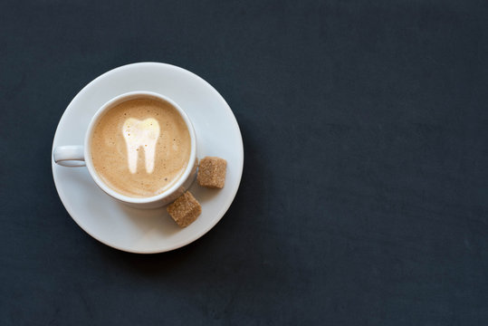 Cup of coffee with milk, cane sugar and tooth sign on dark background. Top viewю Copy space