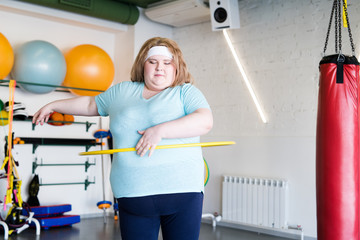 Portrait of  obese young woman exercising with hula hoop during weightloss training in gym, copy space