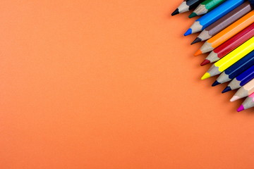 Pencils set on orange tone color paper. Empty space for text and design. Minimalism concept.