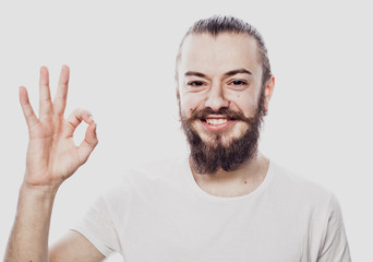 Portrait of a cheerful young bearded man showing okay gesture isolated on the white background