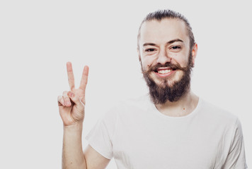 happy bearded man making the victory or peace hand sign on white background