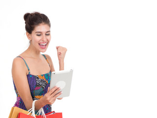 Picture showing pretty woman shopping online with smart tablet.Portrait of young happy smiling woman with shopping bags.