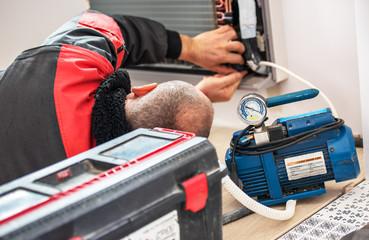Technician vacuum pump evacuates and checking new air conditioner.