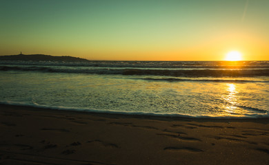 Splendid sunset with footprints on sand and city of Coquimbo on the background in La Serena beach, Chile