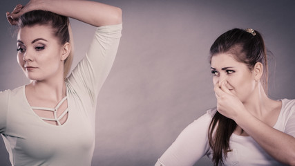 Woman having wet armpit her friend smelling stink