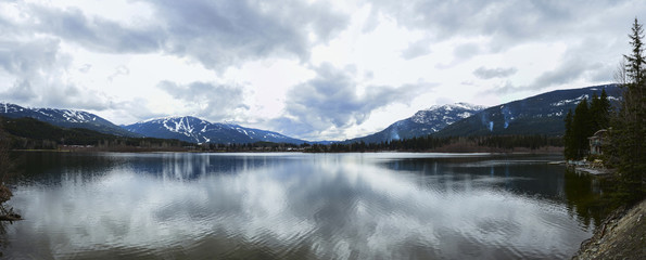 Beautiful mountains view over calm lake and sky reflecting in water, calm vibrant landscape.
