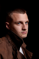 Close-up portrait of young handsome shaved man. on dark background .Modern and dramatic photo.In brown coat. Blue eyes