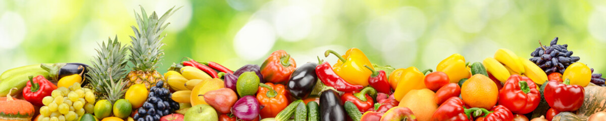 Wall Mural - Panorama of vegetables and fruits on abstract green blurred background.