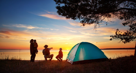 Wall Murals Camping Family resting with tent in nature at sunset