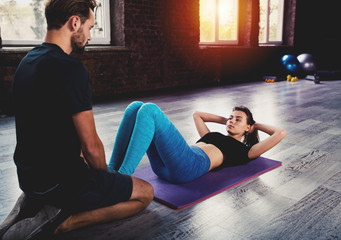Personal trainer helps a girl with the gym exercises