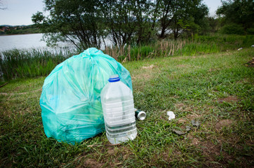 full green garbage bag and open plastic water bottle on the grass in nature by river