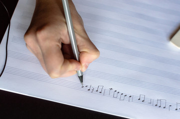 Top view of the hand writing the music notes with pencil. The concept of the music creating, composing, note writing, music art.