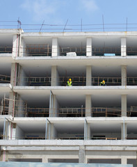 A large construction site of residential apartments with white concrete walls and floors and workers in protective clothing set against a blue sky