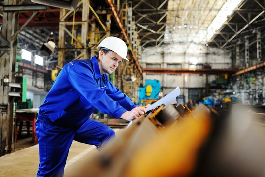Working engineer in a white construction helmet with a project or drawing plan on the background of an industrial plant