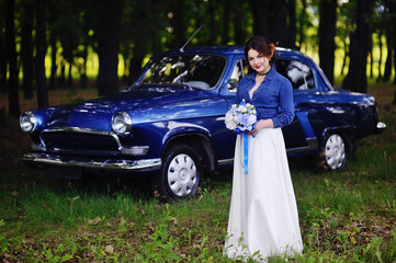 Bride in a denim jacket and with a wedding bouquet near the vintage car
