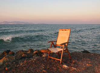An old fading empty wooden chair in reflected sunset light left next to the sea on a calm summer evening