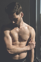 Masculinity and sensuality. Shirtless young stylish thoughtful man is demonstrating his perfect body while posing near window. Sunshine on his torso