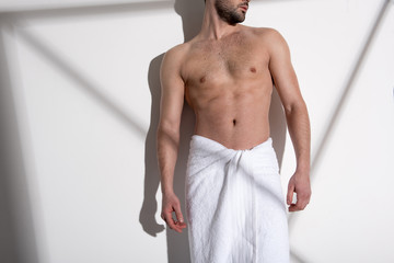 Muscular topless guy with stubble is standing against light background and looking aside thoughtfully. Geometric shadows on the wall