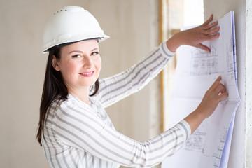 Junge Architektin auf einer Baustelle lächelt sympathisch in die Kamera