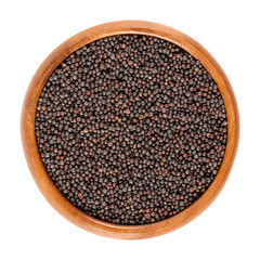 Rapeseed seeds in wooden bowl. Black seeds for sprouting. Brassica napus, known as rape or oilseed rape. Cultivated for its oil rich seeds. Isolated macro food photo, close up, from above, over white.