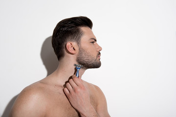 Profile of confident topless guy is standing against white wall and removing unwanted hair from his neckline. He is looking forward seriously. Beauty concept. Copy space in the right side