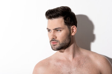 Side view of gorgeous young bearded naked man is standing and looking aside thoughtfully. Copy space in the left side. Beauty concept
