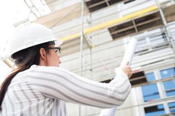 Frau mit Bauhelm auf einer Baustelle