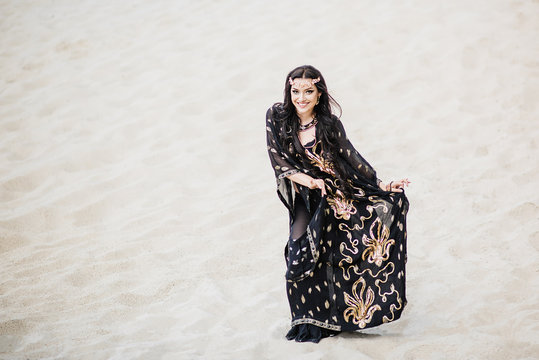 Dancer bellydance and Khaleegy (Khaliji) in a black suit in the desert against the background of sand. Image of Persian Gulf. Beautiful nature. Belly dance. A girl with an exotic look. Eastern beauty.