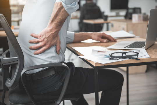 Employer having pain in back. He holding it by hand while sitting at table during job. Worker with bad state of health concept
