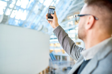 Back view portrait of modern young businessman taking photo of office building, focus on smartphone screen, copy space