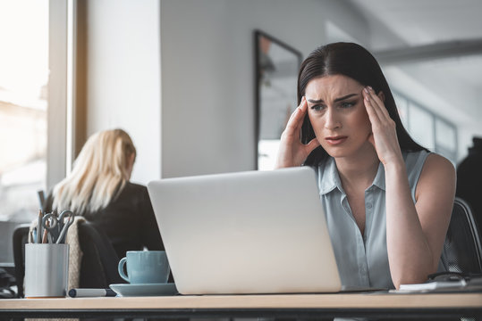 Portrait of disappointed female feeling headache while looking at notebook computer. Unhappy worker concept