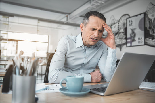 Portrait of depressed male having headache while watching at notebook computer. Frustrated employer concept